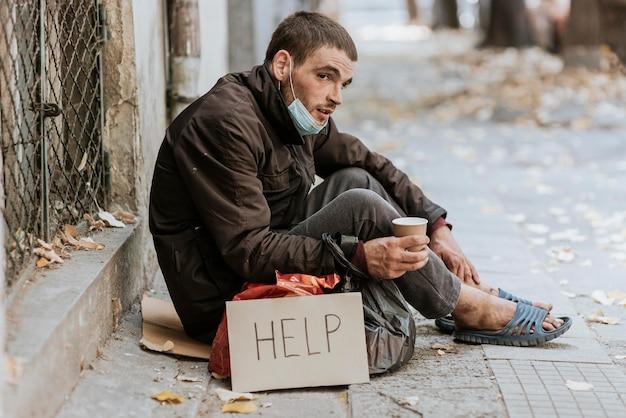 Bezdomny mężczyzna na zewnątrz ze znakiem pomocy i filiżanką