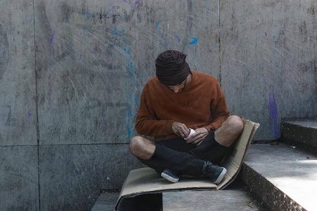 Bezdomny mężczyzna siedzi na tekturze na zewnątrz
