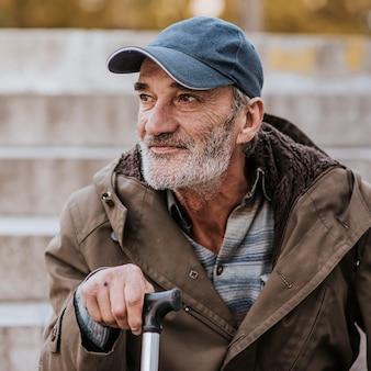 Bezdomny mężczyzna z brodą i laską