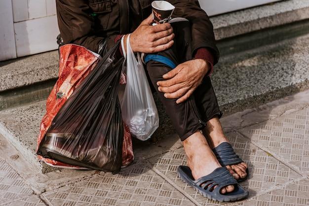 Bezdomny mężczyzna z plastikowymi torebkami i filiżanką na zewnątrz