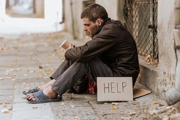 Bezdomny na ulicy z filiżanką i znak pomocy