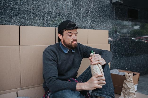 Bezdomny siedzi i opiera się o ścianę z kartonu