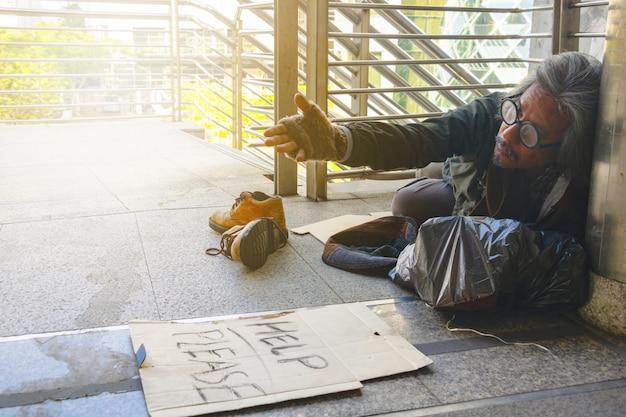 """Bezdomny siedzi na chodniku w mieście. jest to etykieta """"pomóż proszę""""."""