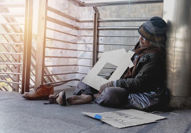 Bezdomny siedzi na chodniku w town.r domu.
