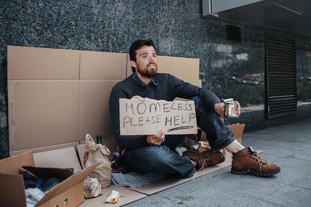 Bezdomny siedzi na tekturze i trzyma znak, że bezdomny proszę o pomoc
