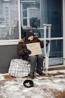 Bezdomny siedzi w pobliżu budynku.