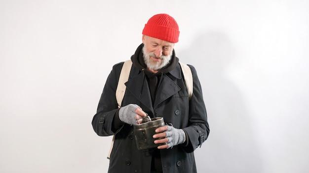 Bezdomny, stary człowiek z siwą brodą w kapeluszu z uśmiechem trzymający w ręku pomoc finansową, dolary, pojedyncze białe tło