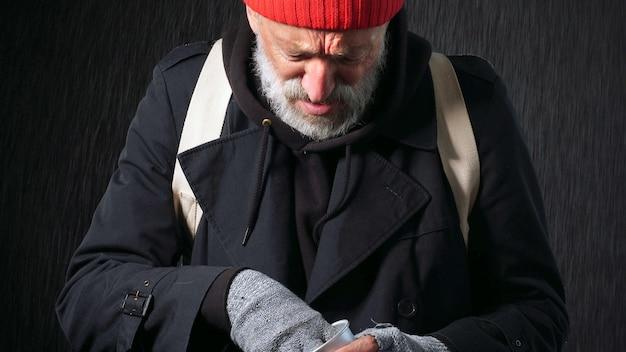 Bezdomny stary człowiek, żebrak, brodaty mężczyzna liczenia monet do jedzenia i picia, na białym tle