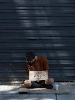 Bezdomny ukrywa twarz i prosi o pieniądze długi widok