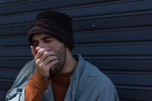 Bezdomny ziewający i zakrywający usta