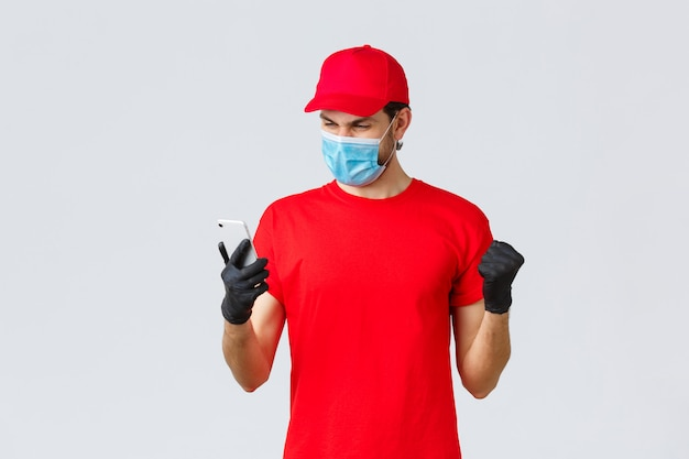 Bezdotykowa dostawa, płatność i zakupy online podczas covid-19, samo-kwarantanna. entuzjastyczny kurier w czerwonym mundurze, masce i rękawiczkach, cieszący się dobrą wiadomością, wygląda na ekranie smartfona