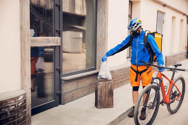 Bezdotykowa usługa dostawy podczas kwarantanny. mężczyzna dostarcza żywność i torby na zakupy podczas izolacji. puka do drzwi i zostawia towar do momentu odebrania przez klienta. bezpieczeństwo, odbiór, utrzymywanie dystansu.