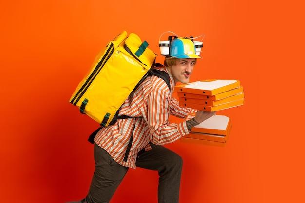 Bezdotykowa usługa dostawy podczas kwarantanny. podczas izolacji mężczyzna dostarcza torby z jedzeniem i zakupami. emocje deliveryman na białym tle na pomarańczowym tle.