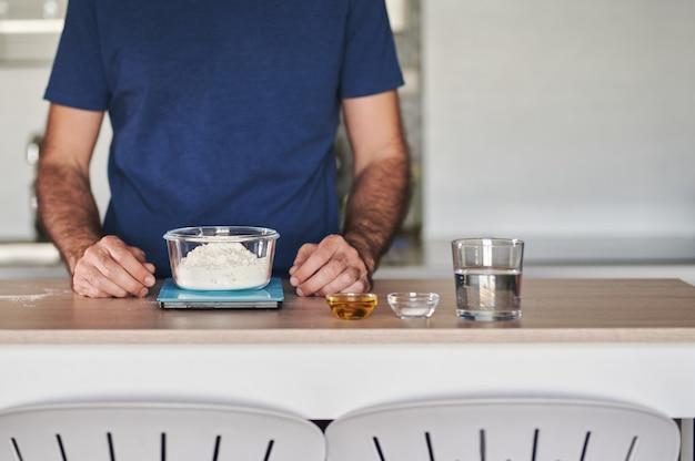 Bezgłowy portret mężczyzny ważącego mąkę w skali cyfrowej do przygotowania ciasta