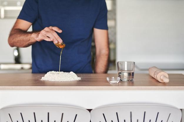 Bezgłowy portret mężczyzny wlewającego oliwę z oliwek na stos mąki