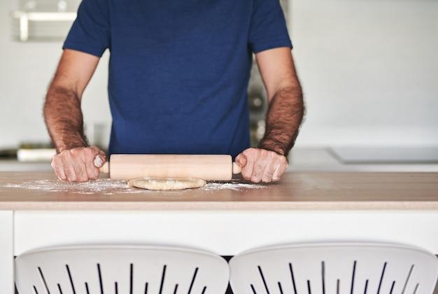 Bezgłowy portret mężczyzny wyrabiającego wałek do ciasta