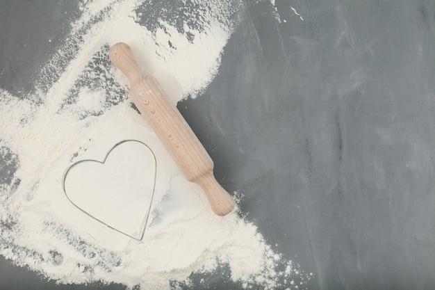 Bezglutenowa mąka migdałowa i drewniany wałek do ciasta na szarym tle z miejsca na kopię.