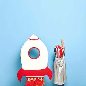 Bezimienne nierozpoznawalne dziecko stoi plecami do aparatu, nosi kask i szarą pelerynę