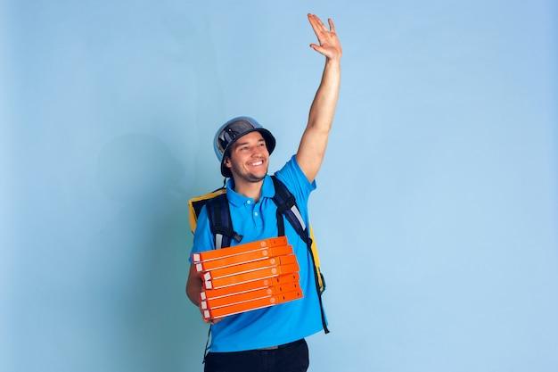 Bezkontaktowa usługa dostawy podczas kwarantanny. mężczyzna dostarcza żywność i torby na zakupy podczas izolacji. emocje odizolowywać na błękicie deliveryman