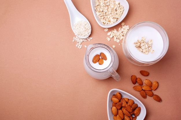 Bezlaktozowe mleko migdałowe, ryżowe i owsiane na beżowym tle. widok z góry