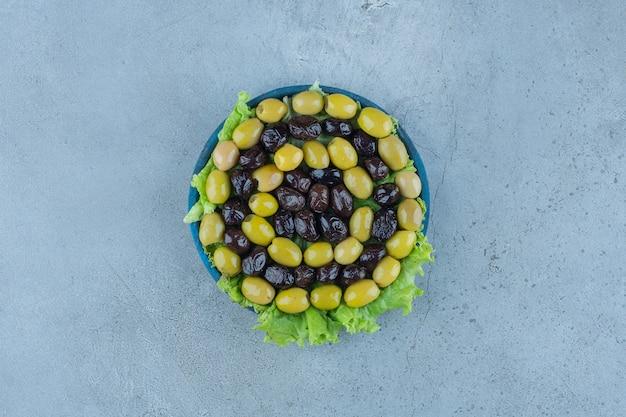 Bezlitosne oliwki na talerzu pokrytym sałatą na marmurze.