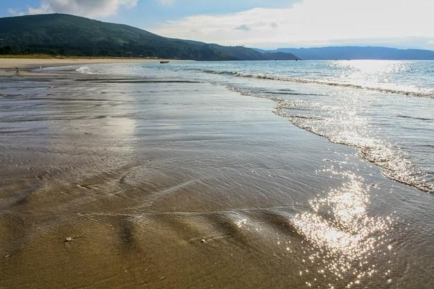 Bezludna plaża z delikatnymi falami na piasku i odbiciem słońca w wodzie.