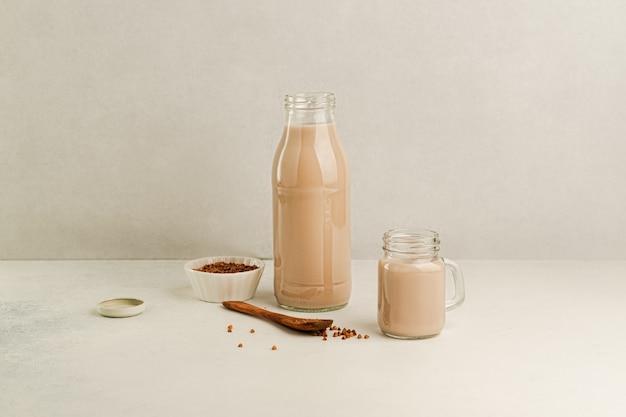 Bezmleczne mleko gryczane w szklanej butelce i słoiku