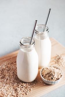 Bezmleczne mleko owsiane w szklanych słoikach z metalowymi słomkami wielokrotnego użytku. zdrowa wegańska alternatywa dla mleka martwa natura, kopia przestrzeń. zamiennik tradycyjnego mleka krowiego z płatkami owsianymi, koncepcja zdrowego stylu życia