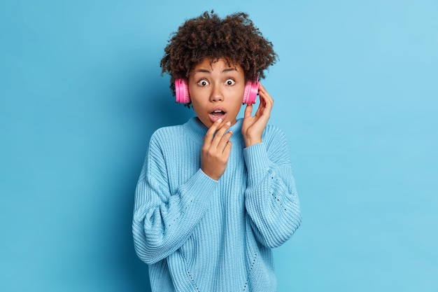 Bezmowa, ciemnoskóra młoda afroamerykańska kobieta jest pod wrażeniem wyrazu twarzy, nosi słuchawki stereo, z otwartymi ustami, ubrana w obszerny dzianinowy sweter