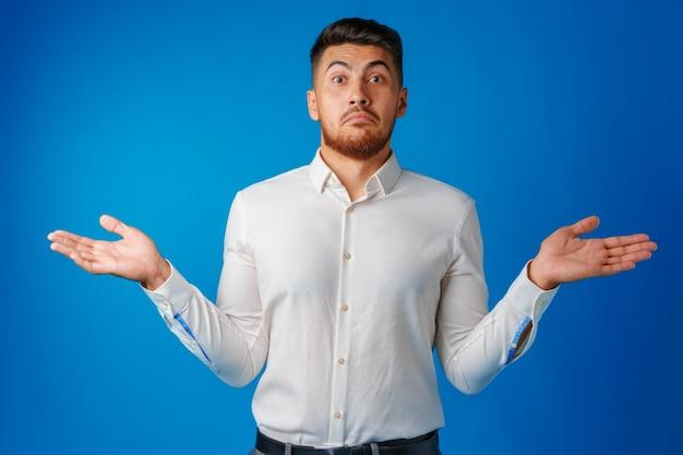Bezmyślny biznesmen gestykulujący, że nie zna, na tle niebieskiego portretu powierzchni