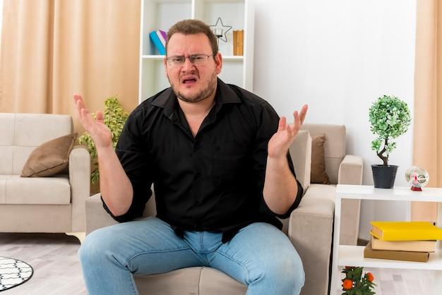 Bezmyślny dorosły słowiański mężczyzna w okularach optycznych siedzi na fotelu z uniesionymi rękami w salonie