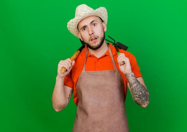 Bezmyślny ogrodnik mężczyzna w kapeluszu ogrodniczym trzyma narzędzia ogrodnicze na ramionach