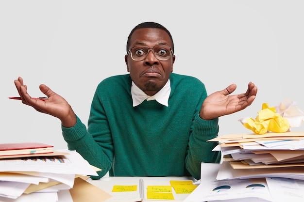 Bezmyślny, zdziwiony ciemnoskóry mężczyzna wzrusza ramionami, czuje się zdezorientowany, ponieważ nie może skończyć zadania, nosi elegancki zielony sweter, nie wie od czego zacząć