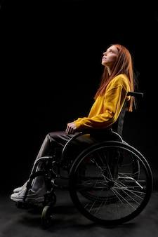 Beznadziejna kobieta siedzi na wózku inwalidzkim nieszczęśliwa, z przygnębionym wyrazem twarzy, cierpi na niepełnosprawność. na białym tle czarna ściana. widok z boku