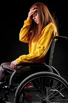 Beznadziejna kobieta siedzi na wózku inwalidzkim nieszczęśliwa, z przygnębionym wyrazem twarzy, cierpi na niepełnosprawność. pojedyncze czarne tło. widok z boku