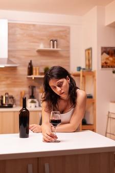 Beznadziejna młoda kobieta pijąca samotnie kieliszek wina w domu czuje się przygnębiona, próbując poczuć się lepiej