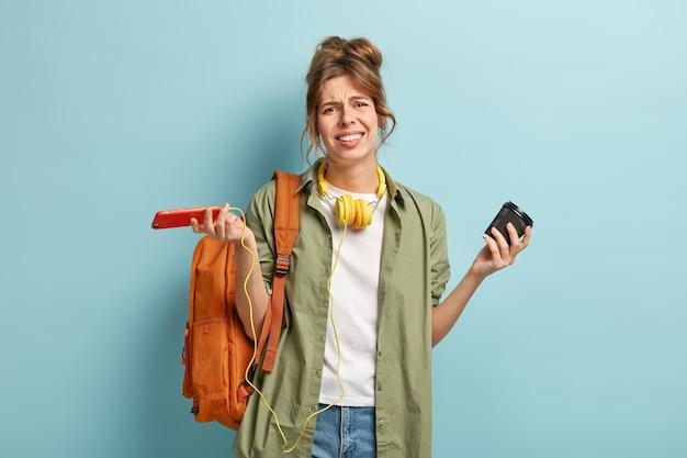 Beznadziejna niezadowolona kobieta patrzy z apatią na aparat, zdenerwowana problemem z oprogramowaniem w aplikacji telefonu komórkowego, rozkłada ręce w tajemnicy, trzyma papierowy kubek z napojem, ma na plecach torbę, uśmiechnięta twarz