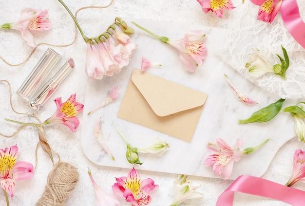 Beżowa koperta na białym stole między różowymi kwiatami widok z góry