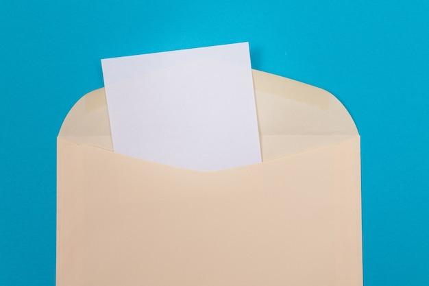 Beżowa koperta z pustą białą kartką papieru w środku