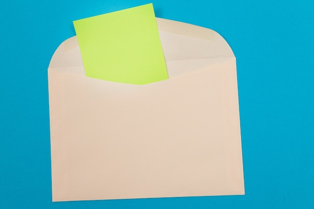 Beżowa koperta z pustą zieloną kartką papieru w środku