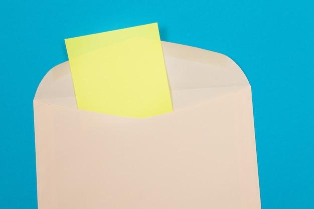 Beżowa koperta z pustą żółtą kartką papieru w środku
