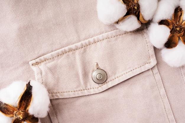 Beżowa koszula dżinsowa i bawełniane kwiaty z bliska, płaski świecki, widok z góry. koncepcja naturalnych, trwałych tkanin bawełnianych. wygodne ubranie dorywczo tło. tkaniny wykonane z materiałów pochodzących z recyklingu.