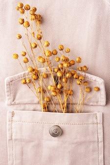 Beżowa koszula dżinsowa i lniane kwiaty z bliska, leżąc na płasko, do obejrzenia. koncepcja naturalnych, trwałych tkanin lnianych. wygodne ubranie dorywczo tło. tkaniny wykonane z materiałów pochodzących z recyklingu.