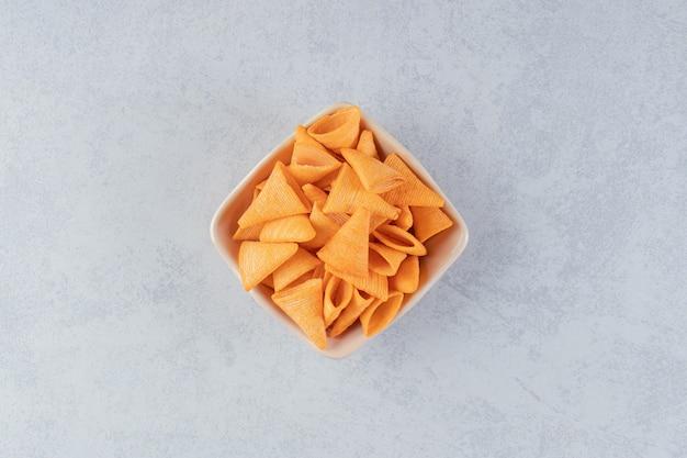 Beżowa miska chrupiących frytek w kształcie trójkąta na tle kamienia.