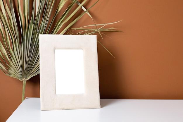 Beżowa ramka copyspace i sucha roślina na białym stole z ciemnopomarańczową ścianą, widok z boku trendu