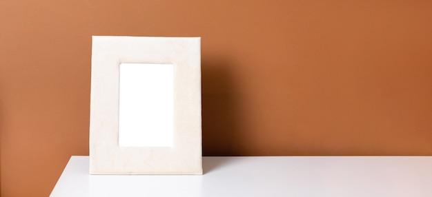 Beżowa ramka copyspace na białym stole z ciemnopomarańczową ścianą, widok z boku projektu trendu