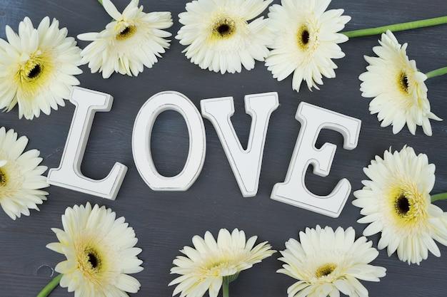 Beżowa ramka z kwiatami gerbery na ciemnym drewnie z literami miłosnymi