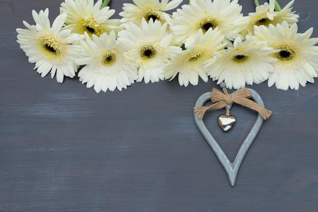 Beżowa ramka z kwiatami gerbery na ciemnym drewnie z sercem
