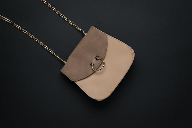 Beżowa skórzana torebka damska z łańcuszkiem na czarnej powierzchni