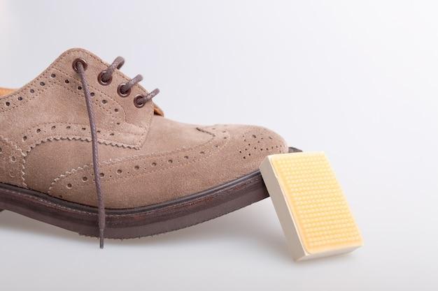 Beżowe buty oxford z gąbką do czyszczenia zamszu na białym